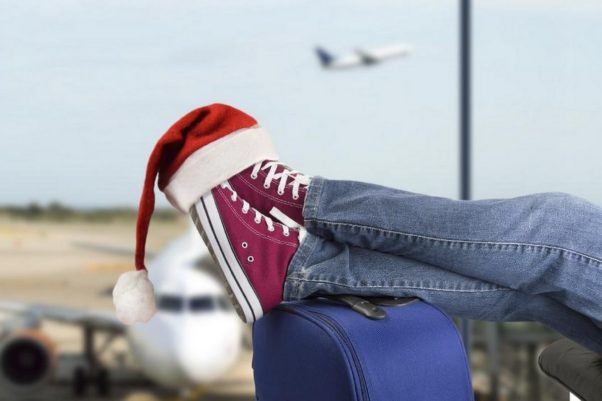 Man's feet in red Converse sneakers propped on a blue suitcase with a Santa hat over the toes and airplanes on the runway out through the window. (Photo: Shutterstock)