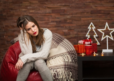 Single woman sitting alone on a bean bag chair beside a table with presents, a metal Christmas tree and a metal star sitting on it. (Photo: Getty Images)