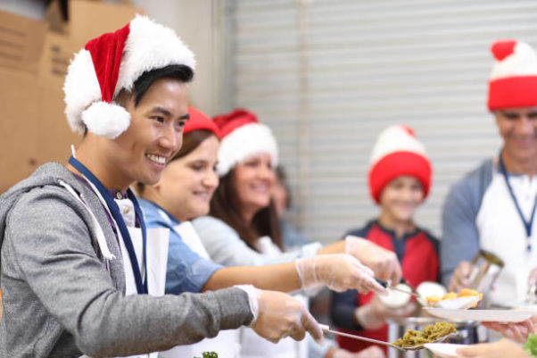 Multi-ethnic, mixed age group of volunteers serves food at a soup kitchen on Christmas. (Photo: Getty Images)