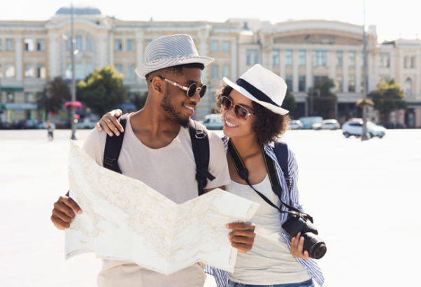Black couples holding a camera and looking at a map while wearing hats, sunglasses and backpacks. (Photo: Dreamstime)Black couples holding a camera and looking at a map while wearing hats, sunglasses and backpacks. (Photo: Dreamstime)