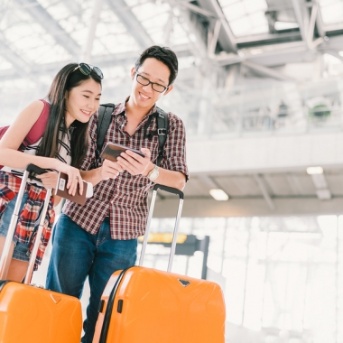 Asian couple in airport checking their cell phone while standing with suitcases. (Photo: Sushiman/Shutterstock)