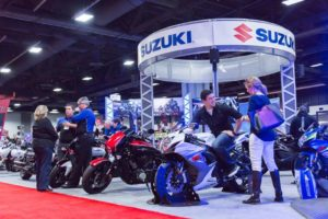 A man sitting on a motorcycle at the Suzuki display while others look at the motorcycles. (Photo: Progressive International Photo Show)