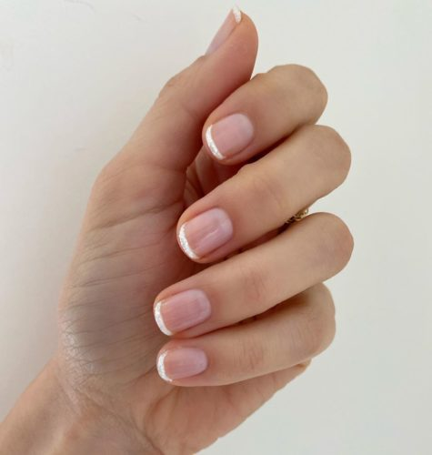 Woamn with a French manicure using white glitter on the tips. (Photo: Betina R. Goldstein/Instagram)
