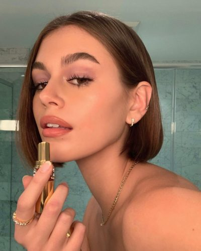 A woman with a bob haircut putting on lipstick. (Photo: Kaia Gerber/Instagram)