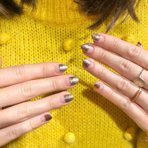 Woman with gold glitter on the top half of her nails and clear polish on the bottom half. (Photo: Shorditch Nails & Academy/Instagram)