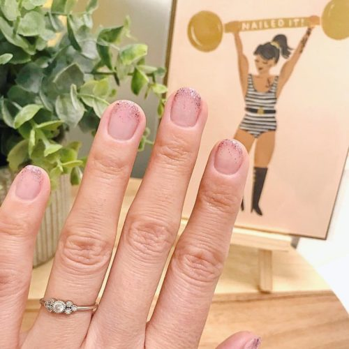Woman with clear glitter on just the tips of her nails. (Photo: Varnish Lane/Instagram)