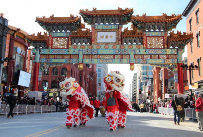 Two sets of dancers in lion cosumes walk under the Friendship Archway in Chinatown. (Photo: Edward Der)