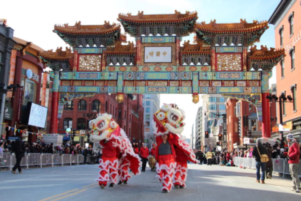 Two sets of dancers in dragon cosumes walk under the Friendship Archway in Chinatown. (Photo: Edward Der)