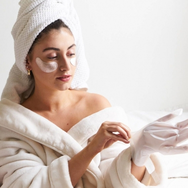Woman in a white robe with towel wrapped around her head applying hand masks. (Photo: skincare.com)