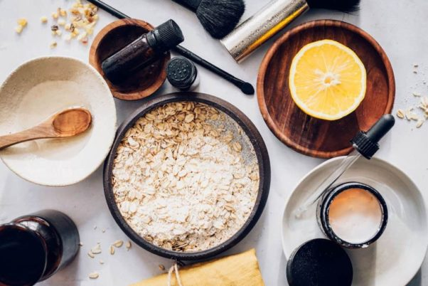 A bowl of oatmeal and a half grapefruid in another bowl sit on a table surrounded by  brushes, jars & more bowls. (Photo: Hello Glow)
