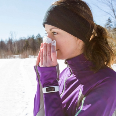 A woman in the snow wearing a purple coat with her hair in a ponytail blowing her nose. (Photo: Getty Images)