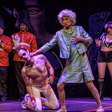 A man dresses as Queen Elizabeth in dress and pearls punches a man on his knees dressed like Freddy Mercury while female referees in shorts and halter tops and palace guards watch. (Photo: AstroPop)
