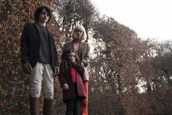 Miles (Finn Wolfhard, left), Flora (Brooklynn Prince, center) and Kate Fairchild (Mackenzie Davis) standing outside looking down at something. (Photo: Universal Pictures)