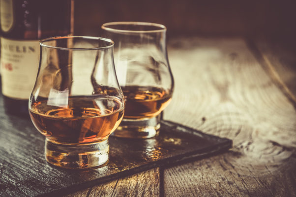 Whiskey with ice in two glasses, rustic wood background. (Photo: Adobe Stock)