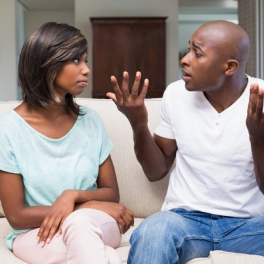 Black couple sitting on a couch arguing. (Photo: Shutterstock)