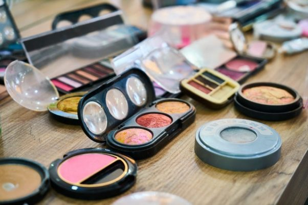 A table covered in different makeup products including powder, eyeshadow, lipstick and blush. (Photo: Engin Akyurt/Pexels)