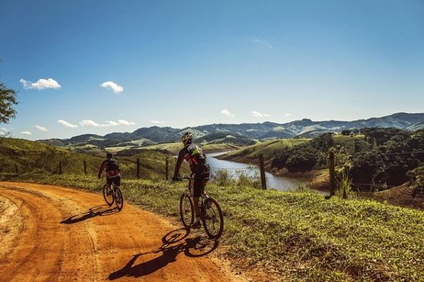 Bicyclists on a dirt road with mountains and a river in the background. (Photo: Fabricio Macedo/Pixabay)