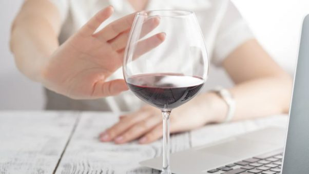 Woman's hand pushing a glass of wine away. (Photo: iStock)