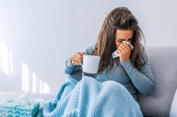 Woman in bed holding a cup of tea and blowing her nose. (Photo: Shutterstock)