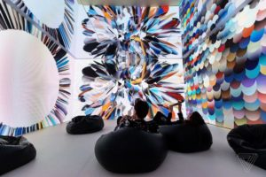 A man and woman sitting in bean bags looking at an abstract projection of colors on the wall. (Photo: Artechouse)