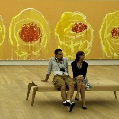 A bored man with a camera around his neck sits next to a woman on a bench who is listening to audio about a painting. (Photo: Digital Cat/Flickr)
