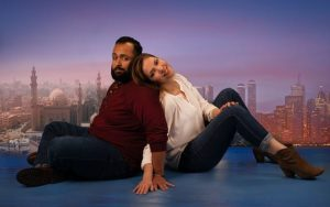 Musa (Ahmad Kamal) and Sheri (Rachel Felstein) sit back-to-bakc on the floor in front of the New York skyline. (Photo; Mosaic Theater Company)