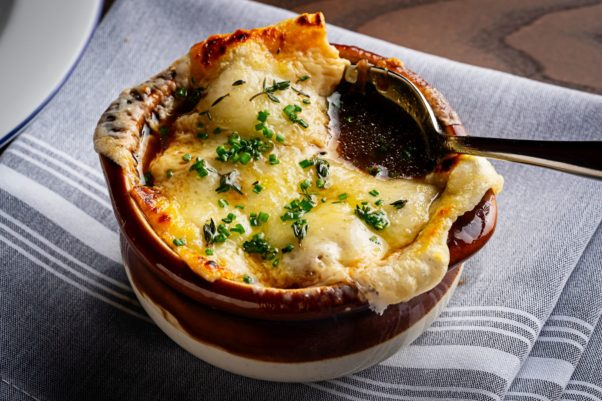 A crock of French onion soup covered in melted Emmental Swiss cheese. (Photo: Scott Suchman)