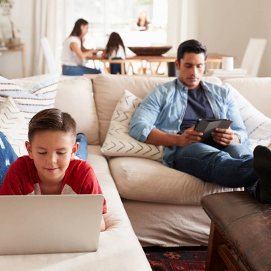 Man sitting on couch with feet propped on table reading tablet while boy lies on stomach using laptop with woman sitting at table in background. (Photo: Getty Images)