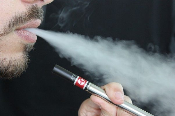 A man blowing out vapor while holding an e-cigarette. (Photo: Lindsay Fox/Pixabay)