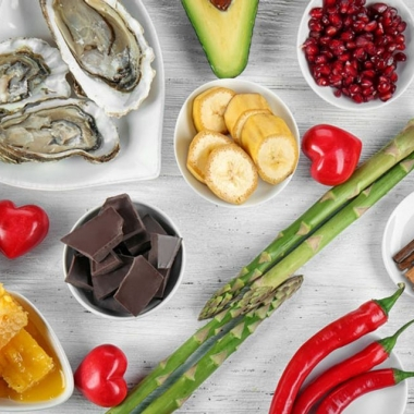 Several aphrodisiacs on a table including oysters, avocados, asparagus, bananas, chocolate and Thai chili peppers, some in heart-shaped bowls. (Photo: Shutterstock)