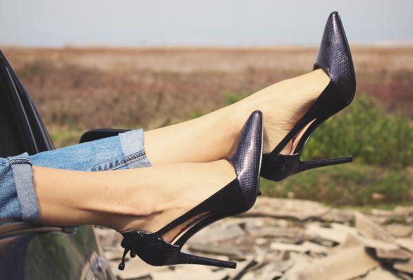 Woman's legs sticking our a car window wearing a pair of black heels. (Photo: Apostolos Vamvouras/Unsplash)