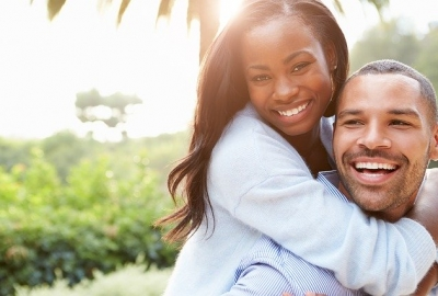 Black couple with him carrying her on his back, both smiling. (Photo: Free-Photos/Pixabay)