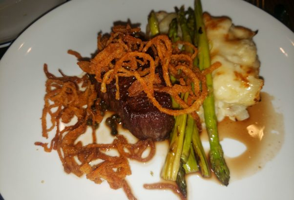 Pepper-crusted fillet mignon au poivre served with horseradish potato au gratin, asparagus and a peppercorn sauce topped with onion strings. (Photo: Mark Heckathorn/DC on Heels)