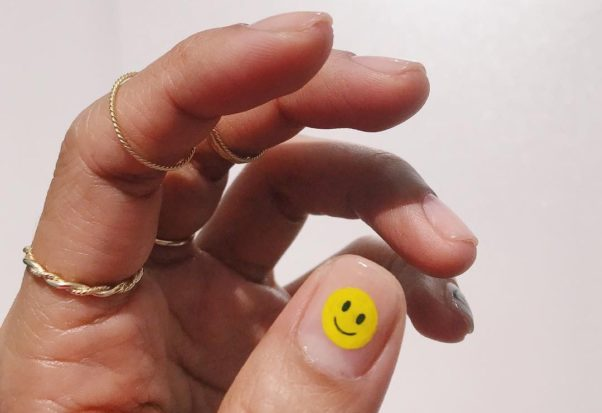 A woman's hand with a happy face on her thumb nail. (Photo: Hang Nguyen/Instagram)