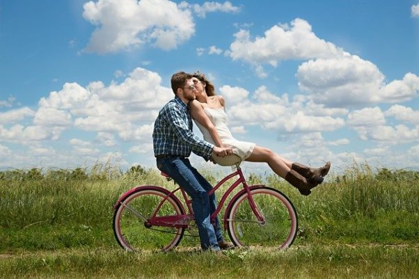 A man stopped on a bicycle kissing a woman sitting on the handlebars. (Photo: Karen Warfel/Pixabay)