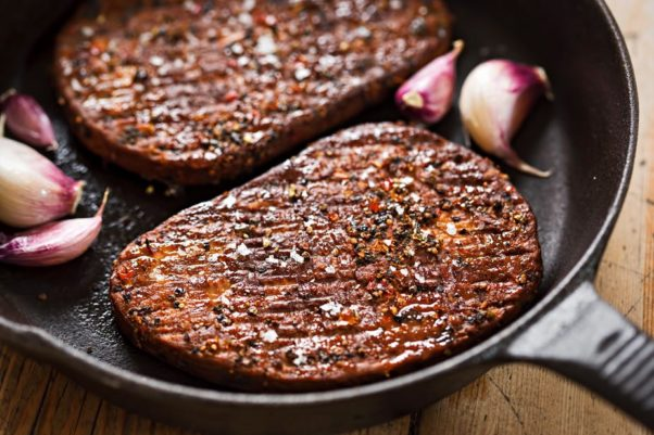 Plant-based steaks in a frying pan with garlic. (Photo: Shutterstock)