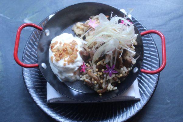 Nameko mushroom rice with stracchiatella, enoki mushrooms and myoga served in a mini black wok with red handles on a black plate. (Photo: Mark Heckathorn/DC on Heels)