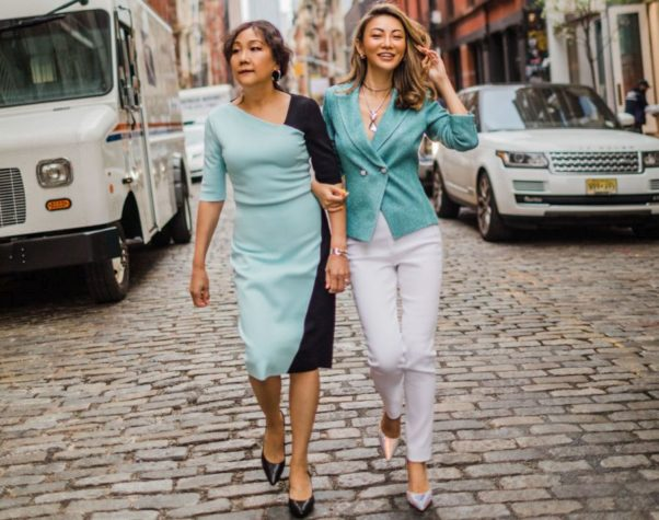 Two Asian women woaking down the street arm in arm. One is wearing a turquise and black dress, the other in a buttoned turquise fitted jacket with white pants. (Photo: Jessica Wang)