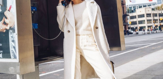 Asian woman wearing a white coat, sweater and pants talking on a payphone. (Photo: Jessica Wang)