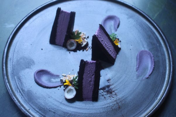 Ube-coconut ice cream sandwich made with purple yam with chocolate and coconut on a white plate. (Photo: Mark Heckathorn/DC on Heels)