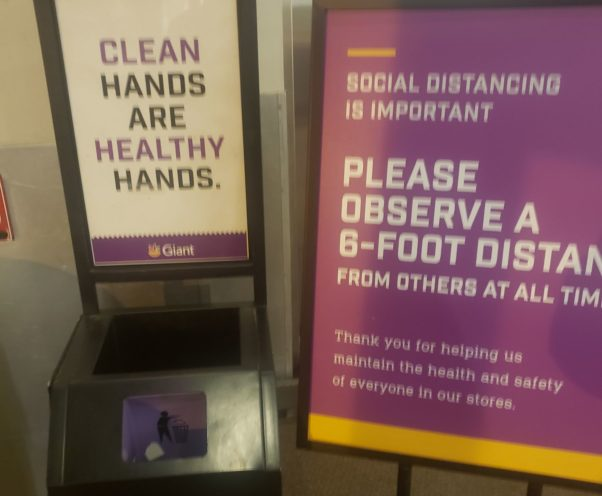 """An empty cart wipe dispenser that says """"Clean Hands Are Healthy Hands"""" sits beside a sign that says """"Please observe a 6-foot distance from others at all times."""" (Photo: Mark Heckathorn/DC on Heels)"""