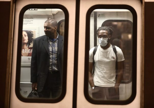 Two African American man seen through the doors on a Metro train. the one on the right is wearing a surgical mask. (Photo: Tyrone Turner/WAMU)