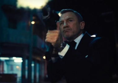 James Bond (Daniel Craig) dressed in a tux firing an automatic rifle. (Photo: Universal Pictures)