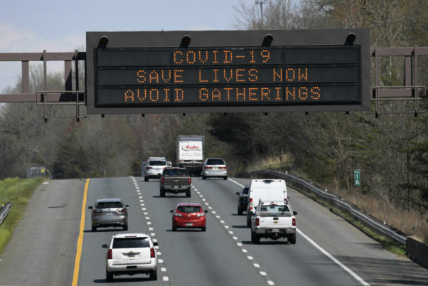 """An electronic sign over Routhe 50 in Davisonville, Md., reads """"COVID-19, Save Lives Now, Avoid Gatherings."""" (Photo: Susan Walsh/AP)"""