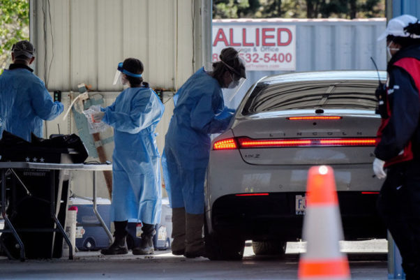 Medical personnel perform drive up tests in the parking lot of United Medical Center on April 2. (Photo: Bill O'Leary/The Washington Post via Getty Images)