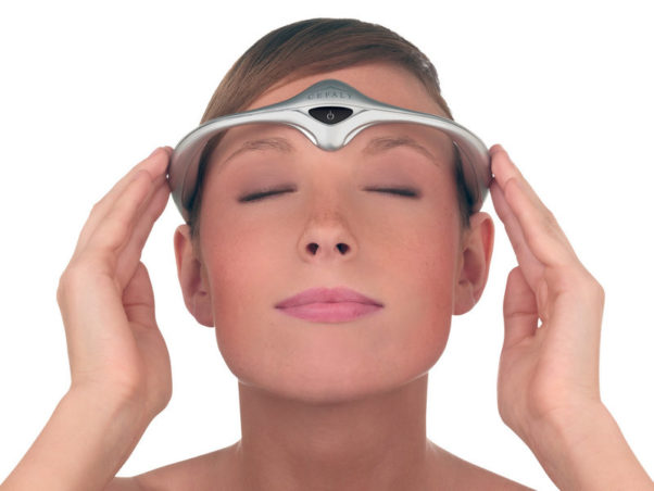 A woman with a Cefaly headband, a medical device that looks like something from Star Trek, on her forehead. (Photo: Cefaly)