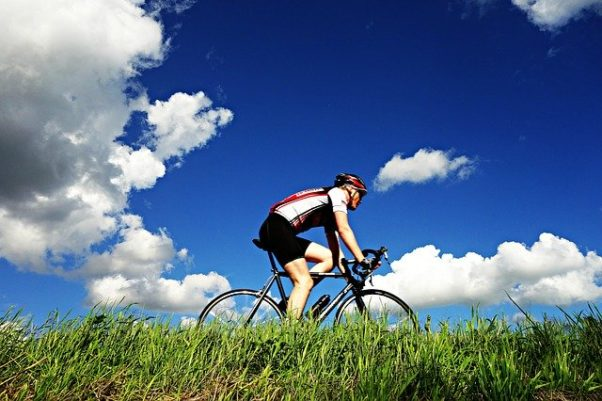 A single cyclist on a bike in a grassy area. (Photo: Mabel Amber/Pixabay)