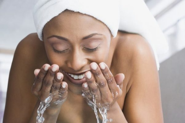 African American woman washing her face with a towel wrapped around her hair. (Photo: Getty Images)