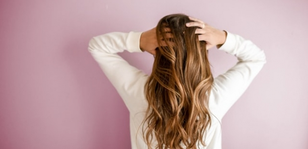 Woman with long hair in white long-sleeved shirt standing in front of pink wall. (Photo: Element5 Digital/Unsplash)
