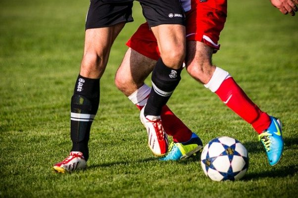 2 soccer players, one dresse din black and the other in red, from the thighs down trying to get the soccer ball. (Photo: Philip Kofler/Pixabay)